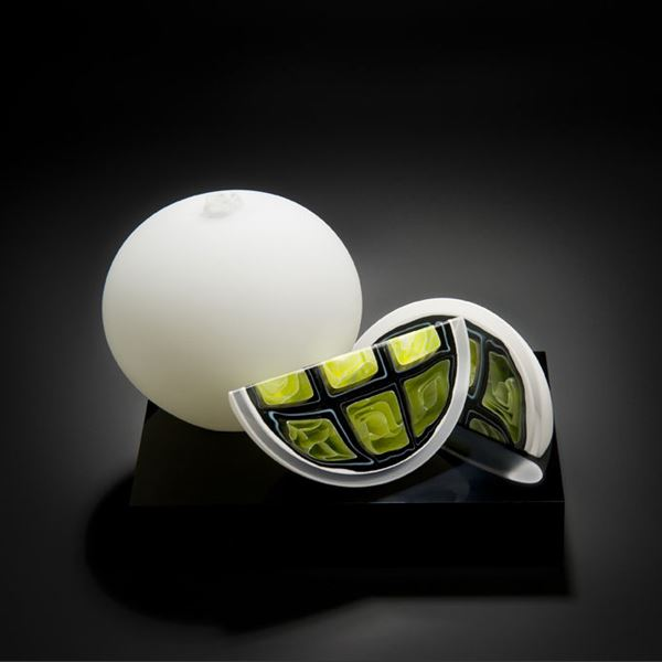 sculpted glass artwork of two fruit in white with one cut to show lime coloured interior