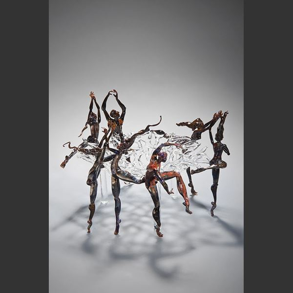 art glass sculpture of figures dancing round central clear glass pane