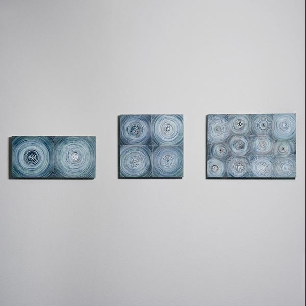 triptych of modern glass wall art with circular patterns in shades of blue and grey