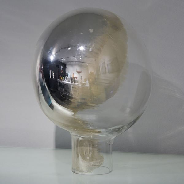 globe shaped minimalist glass sculpture resembling a mirror in white and pearl