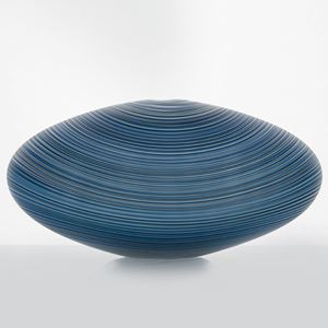 rounded zeppelin shaped glass sculpture with fine line patterned exterior in different shades of blue and grey