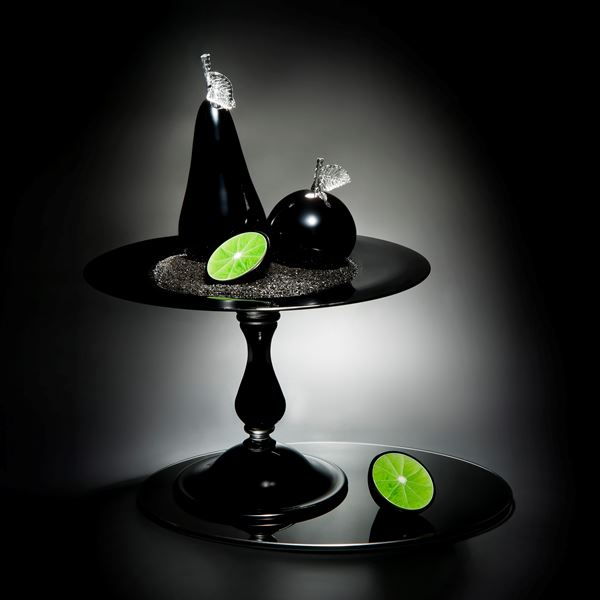 still life sculpted glass scene of cut fruit in black and lime colours