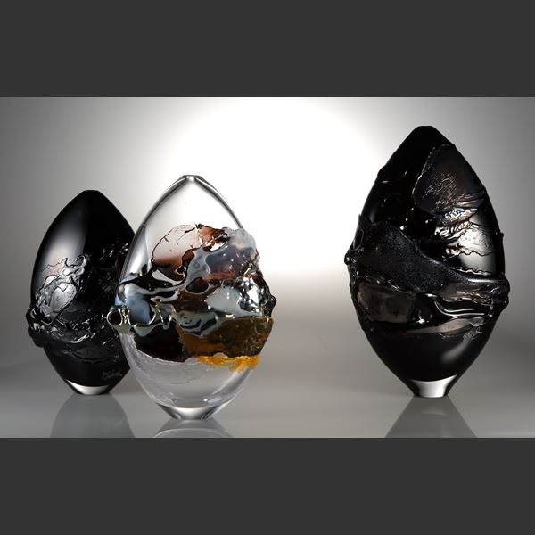 oval shaped black coloured art-glass vessel with external abstract pattern