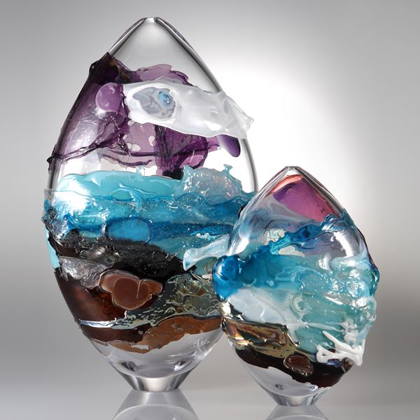 oval shaped clear glass sculpture with turquoise pink and brown splashes of colour