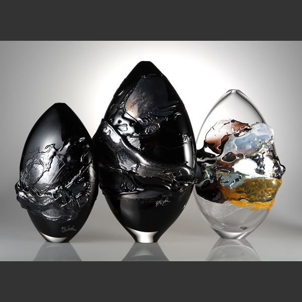 black oval shaped art glass sculptural vessel with gold splashes
