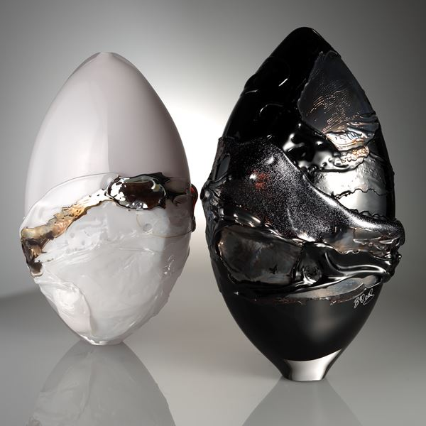 orb shaped art glass sculpture in white with black and gold splashes