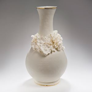 white ceramic vase with wide base and long neck and sculpted flowers