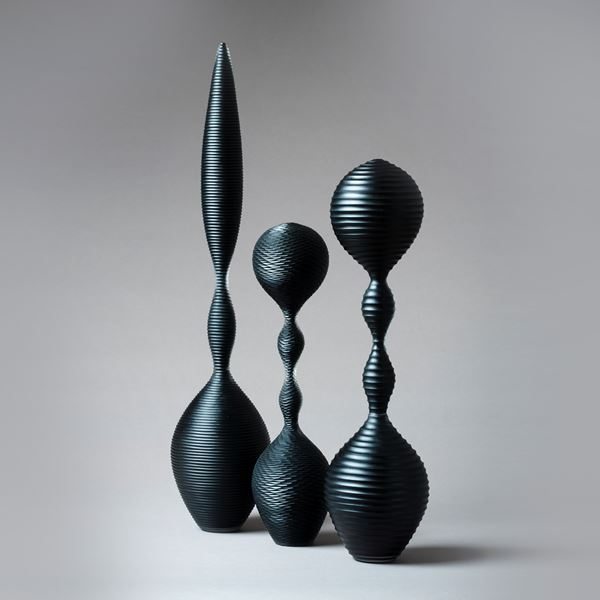 a trio of abstract black sculpted glass ornaments in different sizes