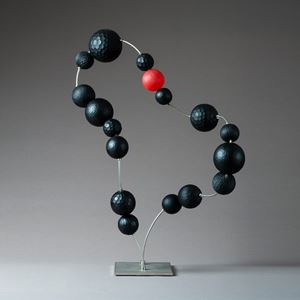 sculpted glass beads in black with one red bead laid out in abstract necklace form on metal base and thread