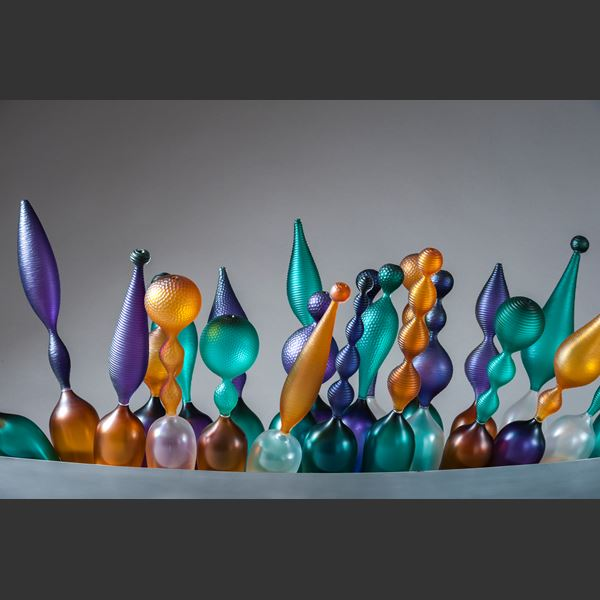 thin art glass sculpted objects in orange purple and green in long grey tray