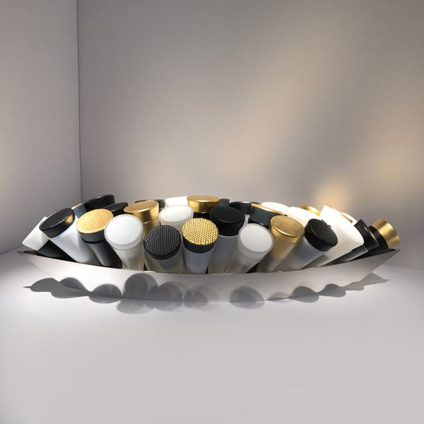 artwork of black white and gold coloured glass tubes in long silver tray.