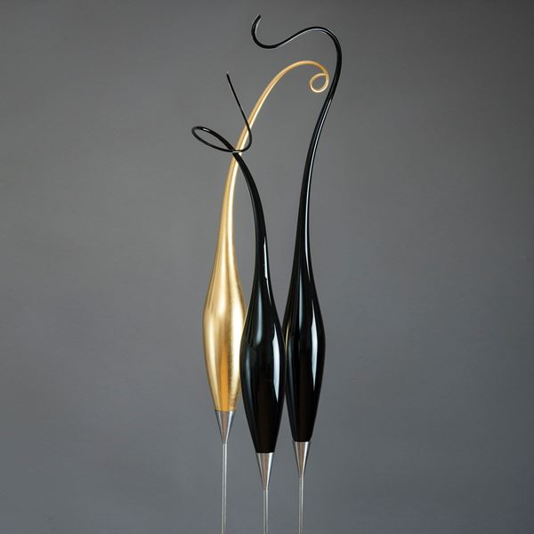 three tall thin glass art strands in black and gold on steel stick bases