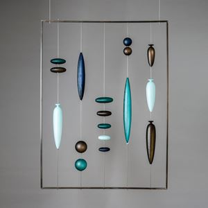 glass hanging wall artwork with small pieces held by wire inside metal frame