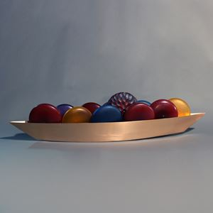 glass artwork of red blue and yellow balls inside steel tray