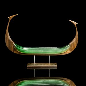 wood and glass sculpture of viking ship in light green and brown on wooden base
