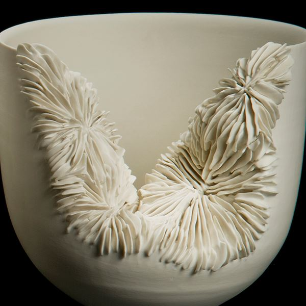 white ceramic sculpture of a tall bowl with collapsed side revealing layered pattern