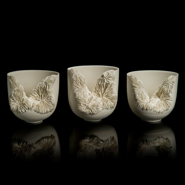 white porcelain sculpted tall bowl with collapsed side recealing complex layered pattern