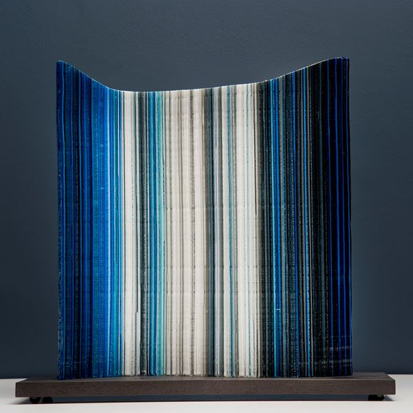 glass artwork resembling barcode in black blue and white on wooden base