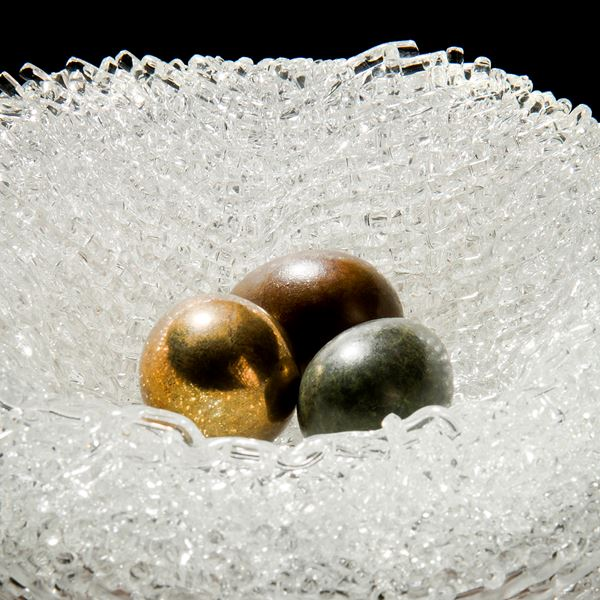 experimental kiln formed art glass sculpture resembling birds nest with three bronze eggs in centre