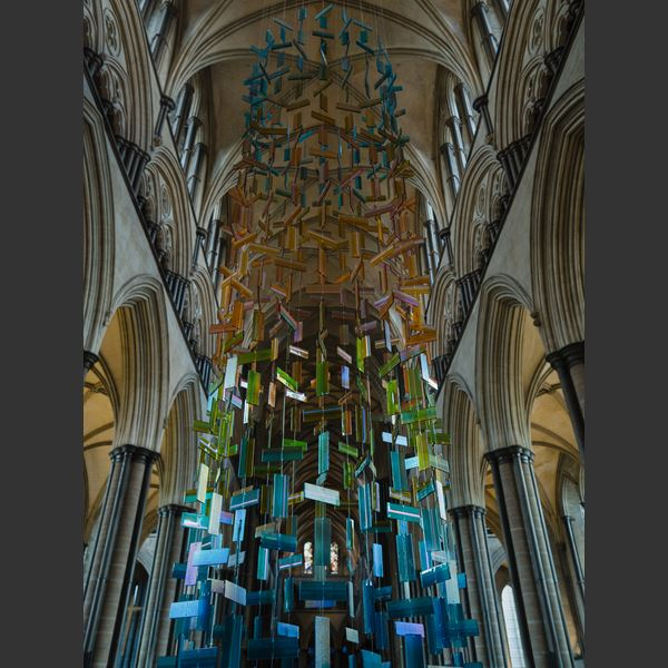 hanging glass installation from handmade fused glass components complementing church stained glass window colours