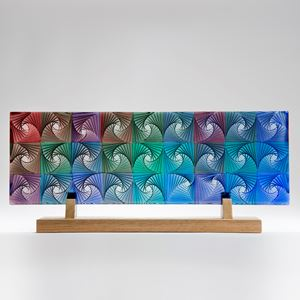 colourful flat rectangular cast glass sculpture resting on wooden base