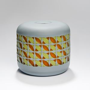round cake shaped glass sculpture in grey with yellow and orange pattern