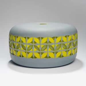 round cake shaped glass sculpture in grey with yellow and gren pattern