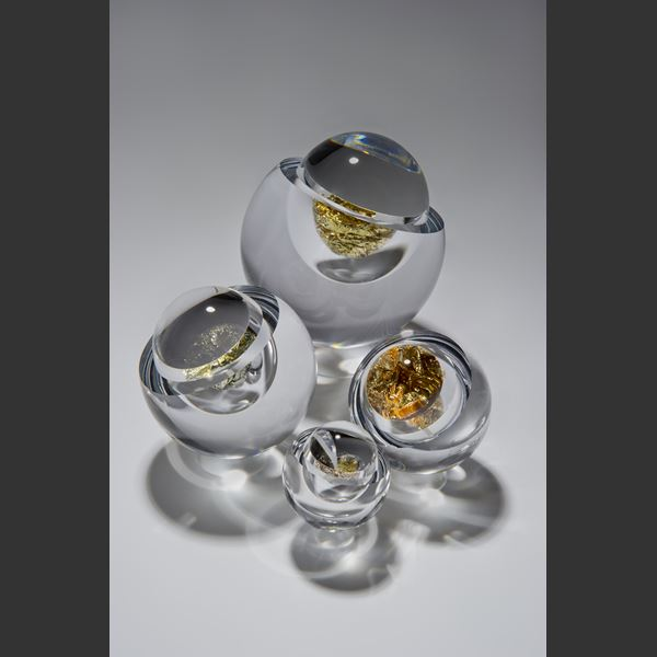 modern art glass orb sculpture with clear glass exterior and yellow gold interior