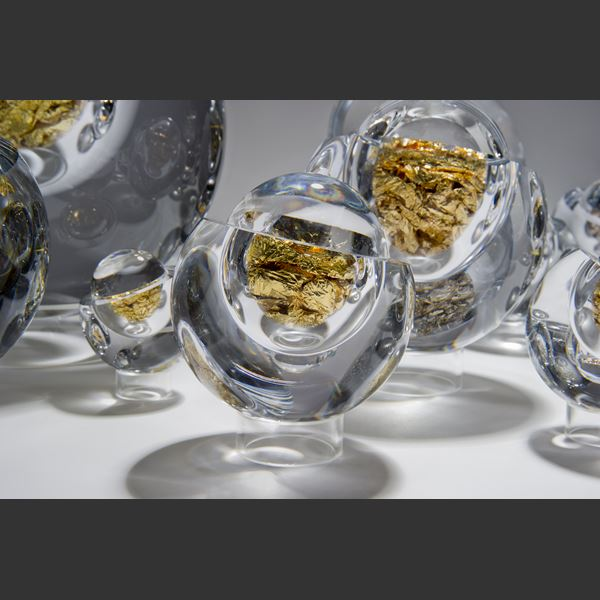 modern art glass orb sculpture in clear glass and white gold