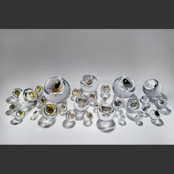 modern art glass sculpture of round object with hole in clear glass and platinum
