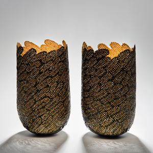 two sculpted open top vessels made from steel and gold cut leaf shapes arranged together