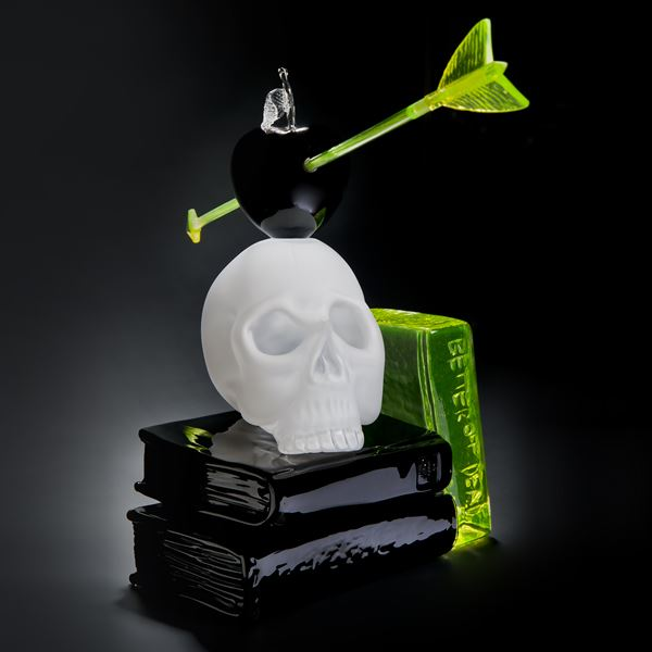 art glass still life sculpture of white skull on black base with neon green arrow through black apple resting on top