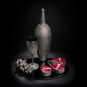 still life artwork of bowl glass grapes and cut fruit in black and dark flesh colours made from handblown and sculpted glass