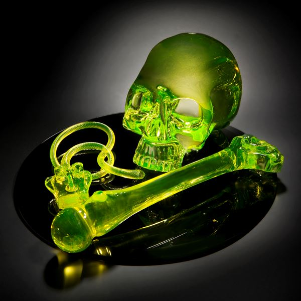 neon green coloured art glass sculpture of skull and bone on black mirror base