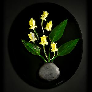 art glass wall sculpture of green leaves and yellow flowers in grey vase with black background