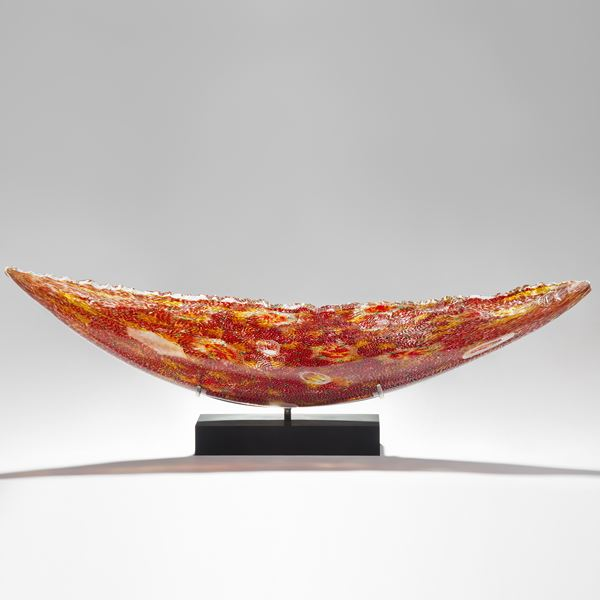 solid glass art sculpture in concave shape with detailled patterns in red and yellow