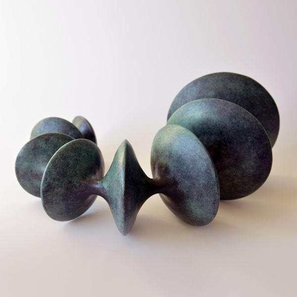 sculpted bronze artwork of circular forms linked by thread