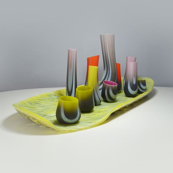 art glass sculpture with flat green base and sprouting shapes in various colours
