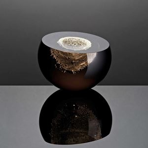 rounded dark glass sculpture with cut top revealing inner details