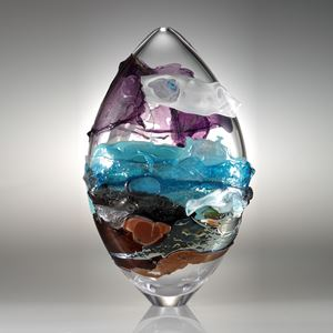 oval shaped handblown clear glass sculpture with purple blue and orange splashes