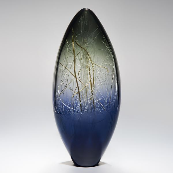 oblong shaped glass sculpture with wire interior in dark blue, green and gold colours