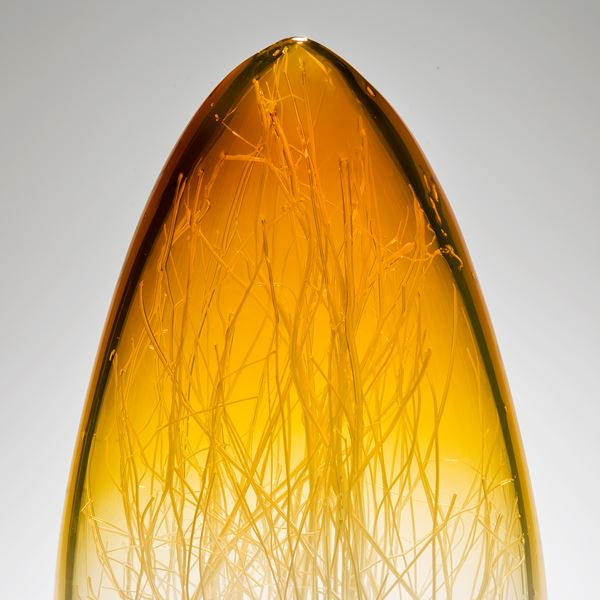 tall sculpted glass vessel in amber and white which wire interior resembling bare tree branches