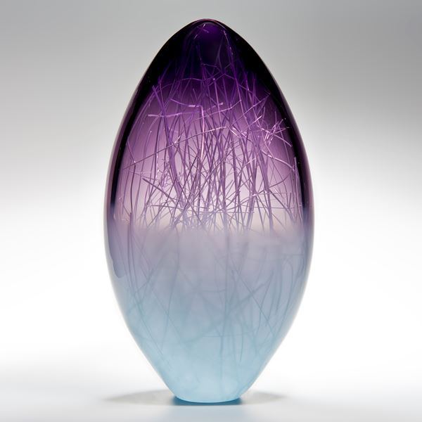 oblong shaped glass sculpture in pale turquoise and indigo with internal wire structure resembling tree branches