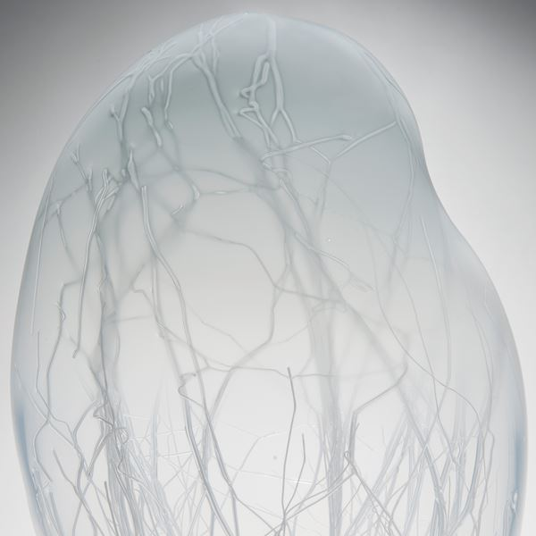 grey floating orb shaped art glass sculpture with internal tree branch structure