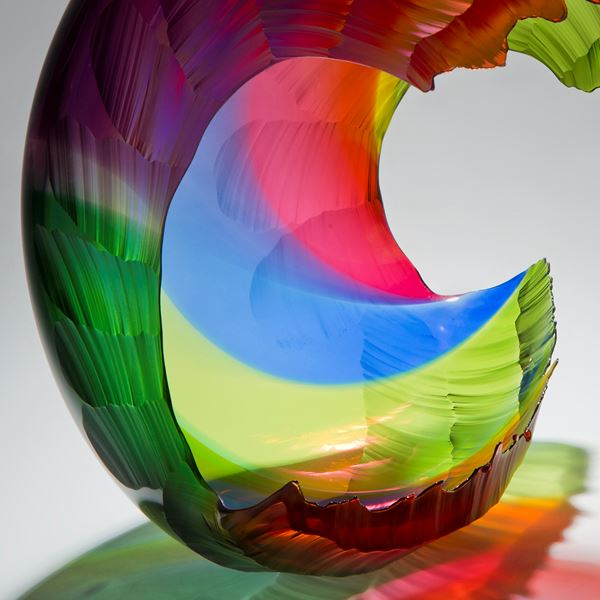 bright multicoloured art glass sculpture in the shape of a wave