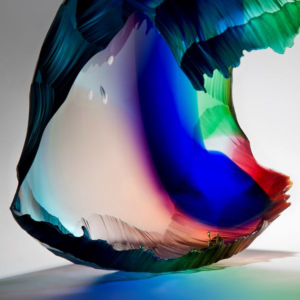 art glass sculpture of wave in bright green blue and red colours