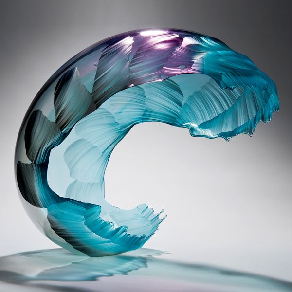 glass art sculpture in form of a wave in bright aqua blue with purple tint