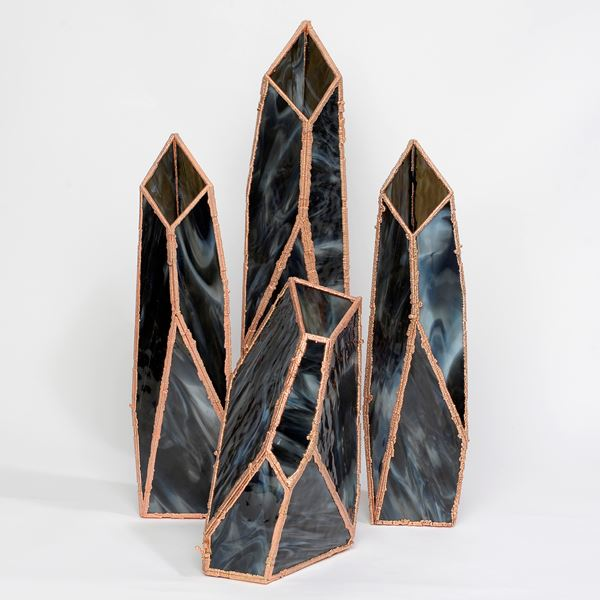 four crystal shaped vases in marbled black with copper frames