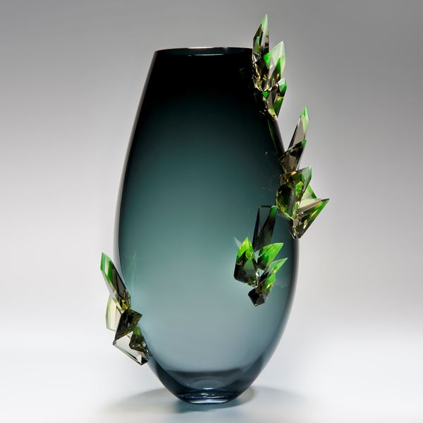 minimalist glass vase sculpture in light to dark turquoise with green external crystals