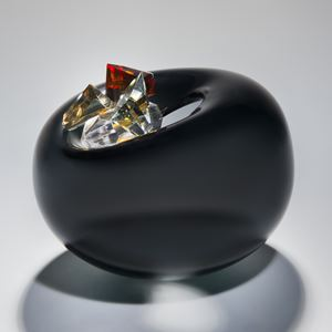 blown glass vase in black in the shape of an apple with red white and gold crystal additions
